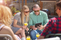 Beautiful stylish friends are using a digital tablet, drinking coffee and smiling while resting in the park.  Royalty Free Stock Photo