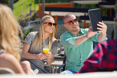 Beautiful stylish friends are using a digital tablet, drinking coffee and smiling while resting in the park.  Stock Photo