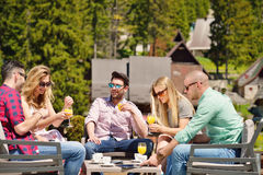 Beautiful stylish friends are using a digital tablet, drinking coffee and smiling while resting in the park.  Stock Image
