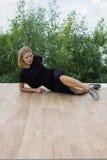 Beautiful stylish girl in a black dress lying on the floor Stock Photo
