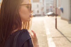 Beautiful stylish girl in a black leather jacket with sunglasses with a dark lipstick in the city at sunset Royalty Free Stock Photos