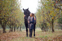 Beautiful stylish girl in a cowboy hat with a horse walking in the autumn forest, country style Stock Photography
