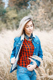 Beautiful stylish girl in denim jacket, checkered red shirt and Royalty Free Stock Images