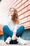 Beautiful stylish girl dreams of the good. Pretty woman in white shoes  sits Royalty Free Stock Image