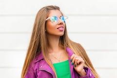 Beautiful stylish girl in fashion sunglasses near a white wall. royalty free stock photos