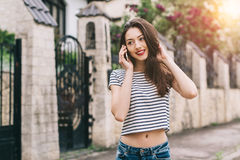 Beautiful and stylish girl with a hat posing on the street and call someone Royalty Free Stock Images