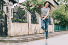 Beautiful and stylish girl with a hat posing on the street and jumping Stock Photos