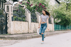 Beautiful and stylish girl with a hat posing on the street and jumping Stock Photo