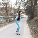 Beautiful stylish girl learns to ride a skateboard Royalty Free Stock Photography