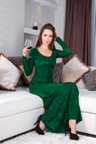 Beautiful stylish girl with long hair in luxury interior posing in stunning evening dress with glass of red wine in her hand. Read Royalty Free Stock Image