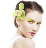 Beautiful stylish girl with orchid flower in hair. Royalty Free Stock Images