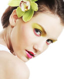 Beautiful stylish girl with orchid flower in hair. Royalty Free Stock Image