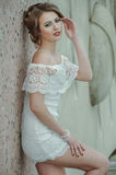 Beautiful stylish girl posing in short white dress against stone wall background. Royalty Free Stock Images