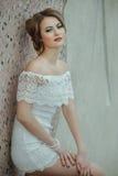 Beautiful stylish girl posing in short white dress against stone wall background. Stock Photo