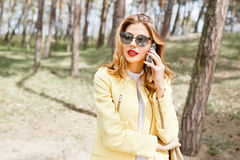 Beautiful, stylish girl on a sunny day in the park talking on th Royalty Free Stock Image