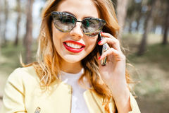 Beautiful, stylish girl on a sunny day in the park talking on th Stock Photo