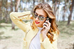 Beautiful, stylish girl on a sunny day in the park talking on th Royalty Free Stock Photos