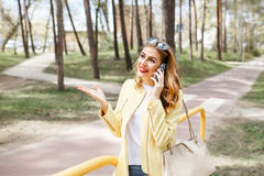 Beautiful, stylish girl on a sunny day in the park talking on th Stock Images
