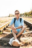 Beautiful stylish guy with glasses, posing sitting on the rails of the train at sunset, hipster posing in stylish clothes, for adv royalty free stock image
