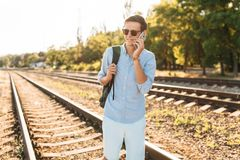 Beautiful stylish guy with glasses, posing on the train rails at sunset, and talking on the phone, hipster posing in stylish cloth stock image