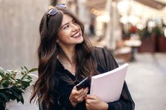 Beautiful stylish hipster girl holding phone and magazine, walki. Ng and smiling in sunny street. happy gorgeous woman, dressed in fashionable outfit, enjoying Royalty Free Stock Photos
