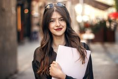 Beautiful stylish hipster girl smiling in sunny city street, hol. Ding magazine. happy gorgeous woman portrait, dressed in fashionable outfit, relaxing and Stock Images