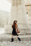 Beautiful stylish hipster woman walking with hat, leather bag, f. Ringe poncho and boots. boho traveler girl in gypsy look, near beach under bridge. summer Stock Photos