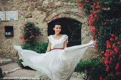 Stylish young brunette bride walking in the summer garden in Ita royalty free stock photo