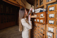 Beautiful stylish lady searching books in the card index.  Vintage library Royalty Free Stock Photo