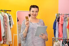 Beautiful stylish overweight woman with tablet and credit card. At shop Royalty Free Stock Photography