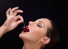 Beautiful, stylish woman eating a dark red cherry Royalty Free Stock Image