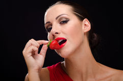 Beautiful, stylish woman eating a strawberry Royalty Free Stock Photo