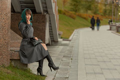 Beautiful stylish woman  in grey coat sitting outdoors Royalty Free Stock Photo