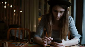 Beautiful stylish woman in hat sitting at the table and using smartphone technology for browsing the Internet. Attractive female spending leisure time in stock video