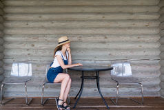 Beautiful stylish woman in jeans dress sitting at a table Stock Image