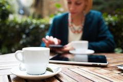Beautiful stylish woman in a suit sitting on the terrace of the office and drinking coffee in your lunch break. Cup of coffee on the foreground with elegant Royalty Free Stock Photo