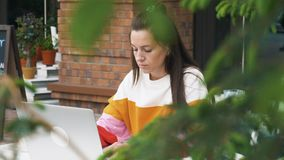 Beautiful woman use laptop in outdoor cafe. Beautiful stylish woman using laptop at the table in outdoor cafe. View from behind a green hedge stock footage