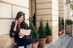 Beautiful stylish woman walking in sunny city street, holding ph. One and magazine. happy hipster girl dressed in fashionable outfit, talking on smartphone in Royalty Free Stock Photography