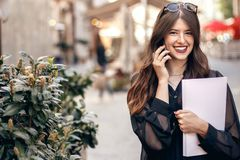 Beautiful stylish woman walking in sunny city street, holding ph. One and magazine. happy hipster girl dressed in fashionable outfit, talking on smartphone in Royalty Free Stock Images