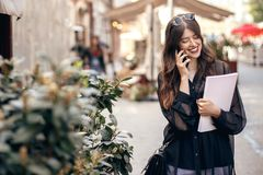 Beautiful stylish woman walking in sunny city street, holding ph. One and magazine. happy hipster girl dressed in fashionable outfit, talking on smartphone in Royalty Free Stock Photo