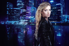 Beautiful and stylish young blonde girl, on the background of night city. Beautiful and stylish young blonde girl on black stock photos