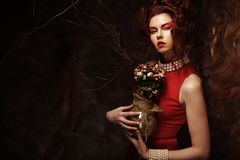 Beautiful stylish brunette in red dress holding a bouquet of dri. Beautiful stylish young brunette in red dress holding a bouquet of dried flowers Stock Photos
