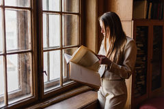 Beautiful stylish young  girl reading a book near the vintage  window in library Royalty Free Stock Images