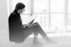 Beautiful stylish young girl reading a book on the windowsill. Black and white photo Stock Image