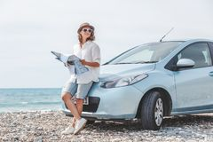 Beautiful stylish young girl travels by car, with a hat and with. A card in her hands, summer travel, freedom, transport for rent, new impressions and adventure Royalty Free Stock Image