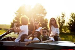 Beautiful stylish young girls and guys in sunglasses are sitting and laughing in a black cabriolet on a sunny day. stock image