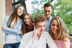 Handsome man calling a phone. Group of teens excited with a mobile on a cafe background. New smartphone concept. Stock Photos