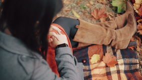 Beautiful, stylish, young womam uses smart clock sitting on plaid in autumn park. 4k stock footage