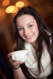 Beautiful woman drinking coffe. Beautiful stylish young woman drinking coffe in a restaurant smiling with pleasure and enjoyment Royalty Free Stock Images