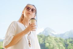 Stylish woman with cup of coffee on background of summer mountains. Beautiful stylish young woman holding cup of coffee in morning on background of summer royalty free stock photos